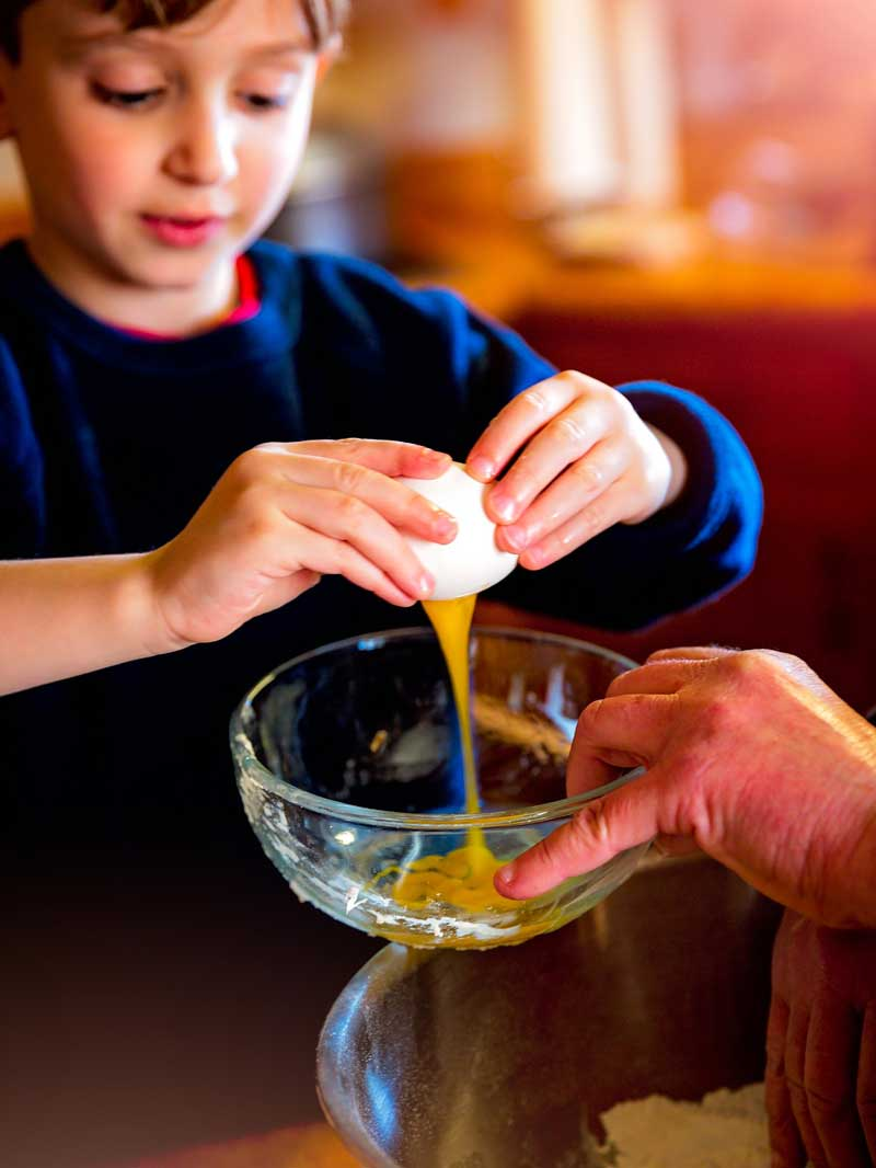 kid cracking an egg in a bowl