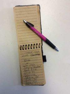 pink pen and tan notepad