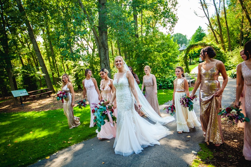 woman in wedding party walking along path underneath green trees