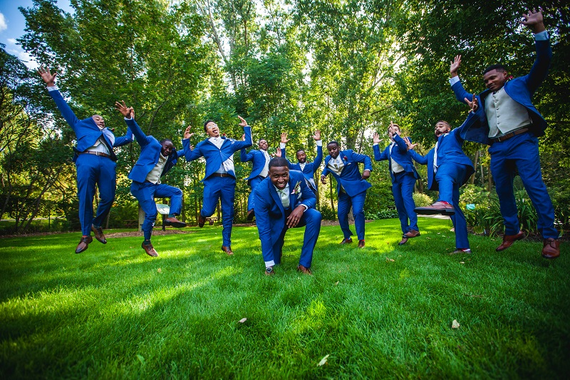 men in wedding party jumping up and down in celebration on green lawn