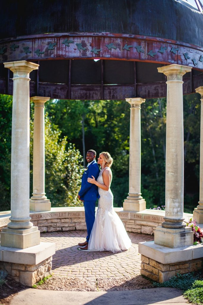 man and woman wedding couple embracing in belvedere structure