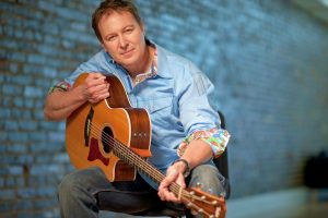 photo of man in blue shirt holding an acoustic guitar