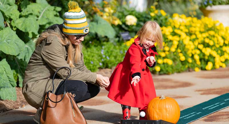 woman with girl in red coat looking at pumpkin