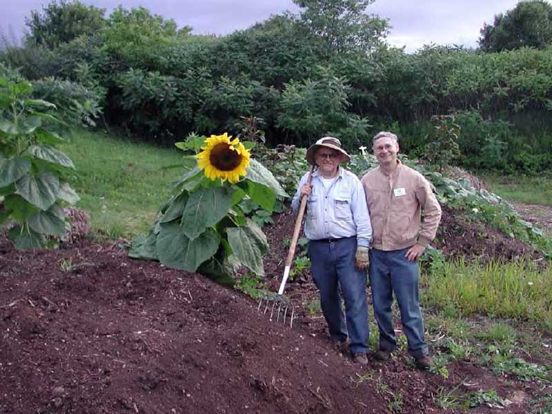 don and lloyd giese posing next to sunflower