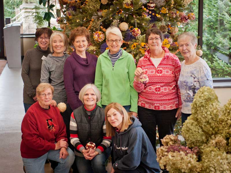 volunteer pose in front of holiday tree decorated with natural items
